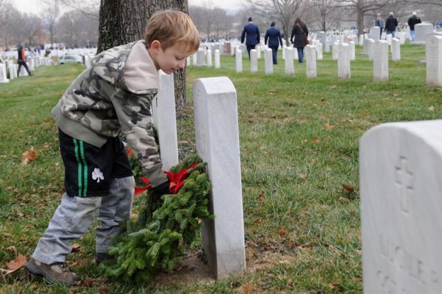 Ben Goodman, 6, places a wreath on a grave, Dec. 15, 2012, at Arlington National Cemetery, Va., as part of Wreaths Across America.
