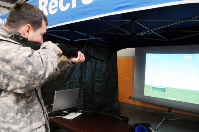 Sgt. Joshua Cooner, 3rd Battalion, 66th Armor Regiment, 172nd Infantry Brigade, attempts to knock birds out of the sky at the shooting simulator at the Info Expo in Vilseck on Dec. 13.