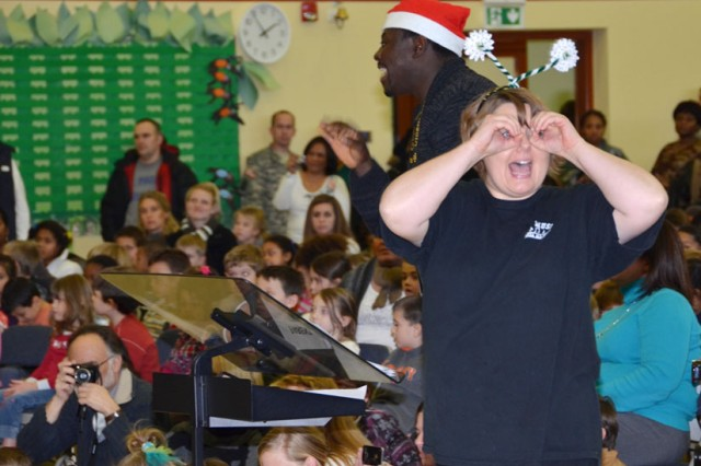 "Music teachers Michael James and Angela Hartwig conduct a chorus of first- and second-graders in a performance of ""A Bugz Christmas"" at Vicenza Elementary School Dec. 12, 2012."