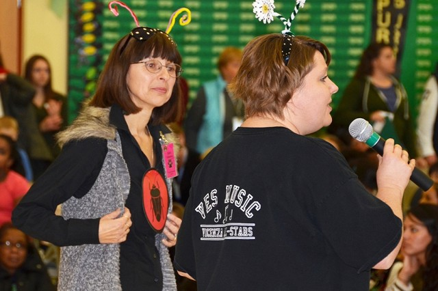 "Community volunteer Branka Lainson (left) and music teacher Angela Hartwig welcome students, parents, faculty and staff to a production of ""A Bugz Chirstmas"" at Vicenza Elementary School Dec. 12, 2012."