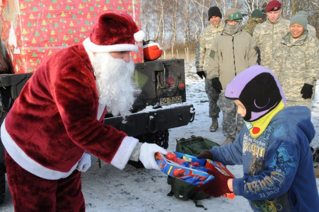 "ALZEY, Germany "" Santa Claus hands out a present during the 5th Quartermaster's Operation Toy Drop at the Alzey Drop Zone, Germany, Dec. 13, 2012. Soldiers, Airmen and partner nation paratroopers jumped into Alzey Drop Zone and donated gifts to needy children from the Kaiserslautern Military Community, Dec. 13."