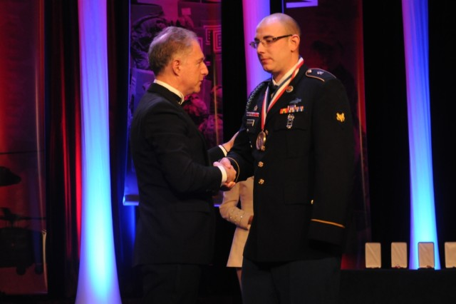 Spc. Bryan D. Dilberian Jr. is presented with the George Van Cleave Military Leadership Award by Lance Boxer, CEO of IPC Systems, at the  51st Annual USO Armed Forces Gala and Gold Medal Dinner.