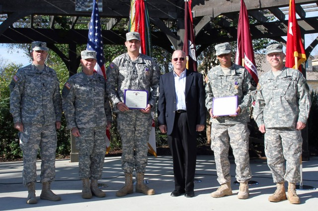 FORT SAM HOUSTON, Texas - Command Sgt. Maj. Hu Rhodes (left), along with Lt. Gen. William Caldwell IV, retired Sgt. Maj. of the Army Jack Tilley and Col. Ronny Fryar, honor the service and sacrifices of Spc. Clayton Stockton (3rd from left) and Pfc. Donnell Lewis (2nd from right) during a Purple Heart ceremony Dec. 11 at the Warrior and Family Support Center in which Stockton and Lewis each were presented the Purple Heart. Caldwell is the commanding general of U.S. Army North (Fifth Army) and senior commander for Fort Sam Houston and Camp Bullis; Rhodes is the command sergeant major of U.S. Army North and senior enlisted leader for Fort Sam Houston and Camp Bullis; Tilley served as the 12th Sergeant Major of the Army; and Fryar is the deputy commander for Allied Health, Brooke Army Medical Center. (U.S. Army photo by Sgt. Lee Ezzell, Army North PAO)