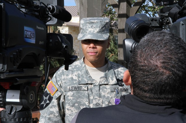 FORT SAM HOUSTON, Texas - Pfc. Donnell Lewis speaks with local television news crews Dec. 11 after he was presented the Purple Heart for injuries he suffered during Operation Enduring Freedom.  Lt. Gen. William Caldwell IV, commanding general, U.S. Army North (Fifth Army), and senior commander, Fort Sam Houston and Camp Bullis, presented Lewis with the Purple Heart during a ceremony at the Warrior and Family Support Center.   (U.S. Army photo by Sgt. Lee Ezzell, Army North PAO)