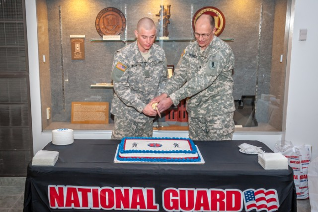 As Fort Leonard Wood's oldest senior ranking and youngest junior ranking members of the National Guard, Staff Sgt. Robert Behrens and Pvt. Galen Heathcock had the honor of cutting the cake for the National Guard's 376th birthday observance Dec. 13 at the Maneuver Support Center of Excellence. The first piece of cake goes to the guest of honor. The second is given to the most senior representative, who in turn passes it on to the most junior representative, signifying the passing of experience and knowledge from the old to the young of our Army.