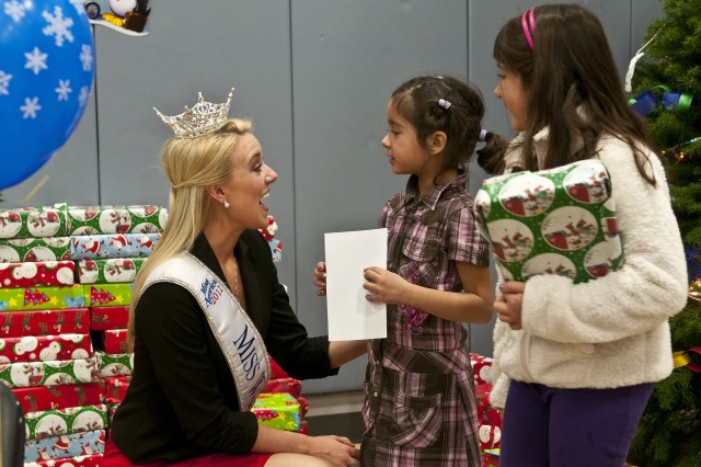 Sydney Flores (far right), 8, and her younger sister visit Dec. 15 with Mandy Schendel, Miss Washington 2012, at the annual Holiday Fest event offered by the Hillside Youth Center on Joint Base Lewis-McChord, Wash. It was the first trip onto a military installation for the 22-year-old pageant beauty, who explained that it was an honor to bring a little dose of cheer to service members and their Families.