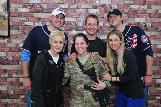 Spc. Tasha Wilson, assigned to Third Infantry Division, poses for a group photo with memebers of the annual USO holiday tour, Dec. 16, 2012, after a private dinner with the celebrities at Kandahar Airfield, Afghanistan.