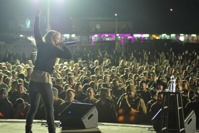 NBC's Last Comic Standing season six winner Iliza Shlesinger raises her fist adding emphasis to her joke, Dec. 16, 2012, bringing smiles and laughter to deployed service members at Kandahar Airfield, Afghanistan.