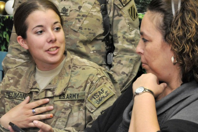 Pfc. Elizabeth Neuman, 502nd Military Intelligence Battalion, talks with Lisa Battaglia, wife of the senior enlisted adviser to the Chairman of the Joint Chiefs of Staff, during a female engagement team luncheon at the Luxembourg dining facility, Kandahar Airfield, Afghanistan, Dec. 16, 2012.