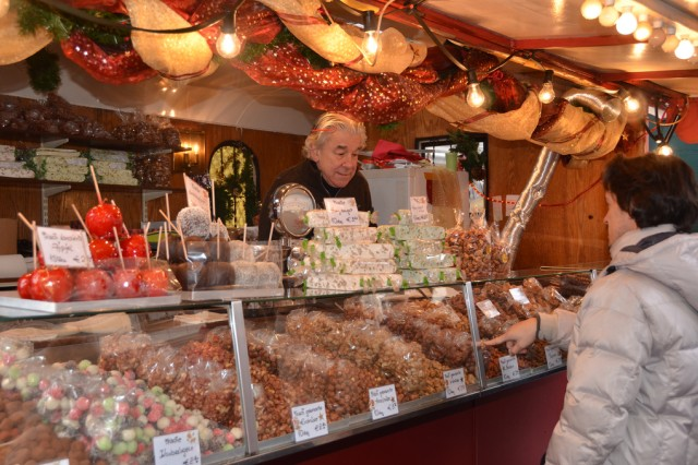 Shoppers Buy Bags Of Flavored Nuts And Sweets From A Vendor At The Innsbruck Christmas Markets