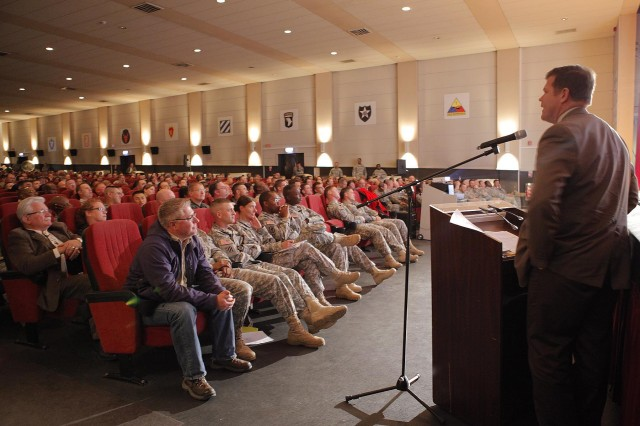 Steven Lindstrom, Joint Multinational Training Command (JMTC) Intelligence and Security Chief addresses a packed auditorium on Oct. 24, at the Tower Theater in Grafenwoehr.