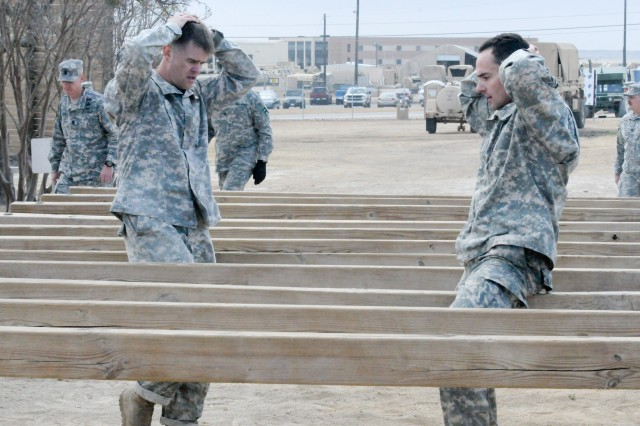 Capt. Grant Flynn (left) and Capt. Andrew Sidwell, with the 1-393rd Infantry Battalion, 479th Field Artillery Brigade, Division West, navigate an obstacle course at Fort Hood, Texas, Dec. 4, 2012, during validation training for the 30th annual Best Ranger Competition. The two officers were selected to represent First Army in the competition to be held in April 2013.