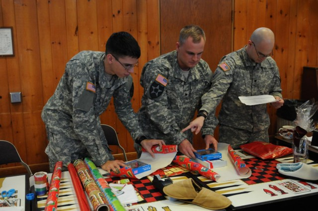 Pfc. Joaquin Oronoz, Spc. Evan Rutledge and Spc. Richard Jensen wrap presents to be sent to family of the residents at the Washington Soldiers Home. The Soldiers of 2-3 Inf., as well as members of the American Legion Auxiliary, assisted the residents at the Soldiers Home with selecting the gift that will go to the veteran's family, wrapping the present and ensuring it was properly packaged and mailed off the same day to their loved ones.