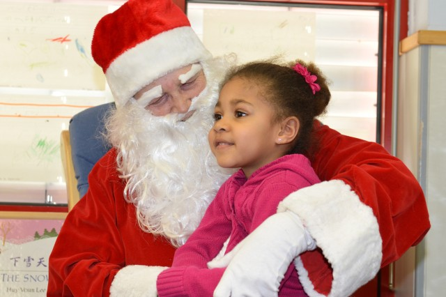Dressed as Santa Claus, Gerda Welch asks a child from the Wetzel Child Development Center if she's been good this year and deserving of a gift. Of course the answer was yes.