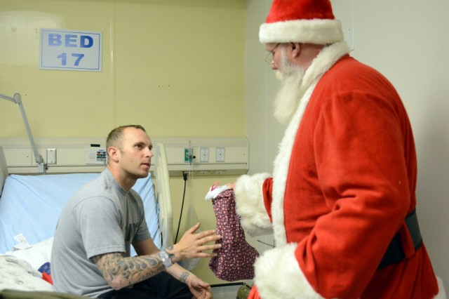 """BAGRAM AIRFIELD, Afghanistan """" Santa Claus gives a Christmas stocking to wounded warrior Spc. Joseph Beldon at the Craig Joint Theater Hospital at Bagram Airfield, Afghanistan, Dec. 18, 2012. (U.S. Army photo by Staff Sgt. David Overson, 115th Mobile Public Affairs Detachment)"""