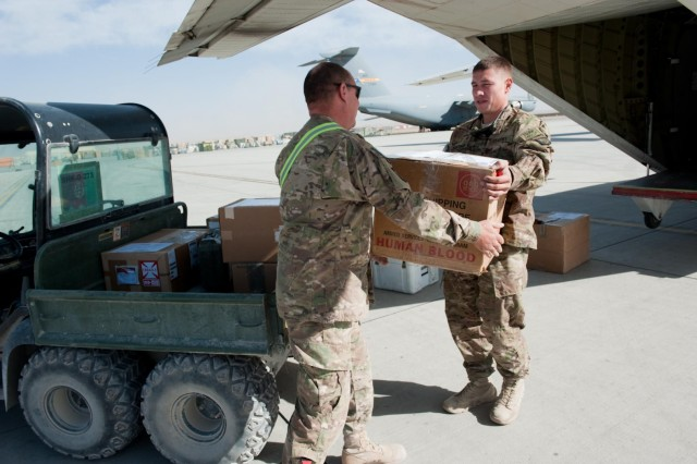 Sgt. Simon Santiago, Headquarters Support Company, 96th Aviation Support Battalion, 101st Combat Aviation Brigade, Task Force Troubleshooter, hands off a box of blood to a Soldier with Task Force Eagle Assault, as part of a routine delivery at Forward Operating Base Shank, Afghanistan, Oct. 6, 2012.