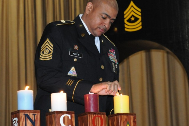 "CAMP HUMPHREYS "" Command Sgt. Maj. Robert F. Austin of the 19th Expeditionary Sustainment Command lights the last candle during the 94th MP NCO induction Ceremony held at the Humphrey's theatre December 12. (U.S. Army photo by Staff Sgt. Robert DeDeaux 501st  SBDE Public Affairs)"
