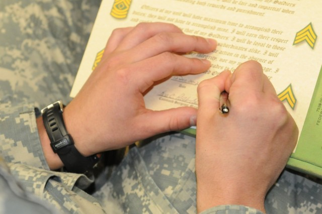 """CAMP HUMPHREYS """" An Noncommissioned Officer signs the Creed of the Noncommissioned Officer preceding the 94th MP NCO induction Ceremony held at the Humphrey's theatre December 12. (U.S. Army photo by Staff Sgt. Robert DeDeaux 501st  SBDE Public Affairs)"""