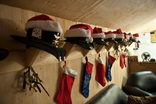 Stetsons adorned with Christmas hats and unit badges hang neatly in a row alongside spurs and stockings as the Yuletide season approaches at Forward Operating Base Fenty, Afghanistan, Dec. 12. (U.S. Army photo by Sgt. Duncan Brennan, 101st CAB Public Affairs)