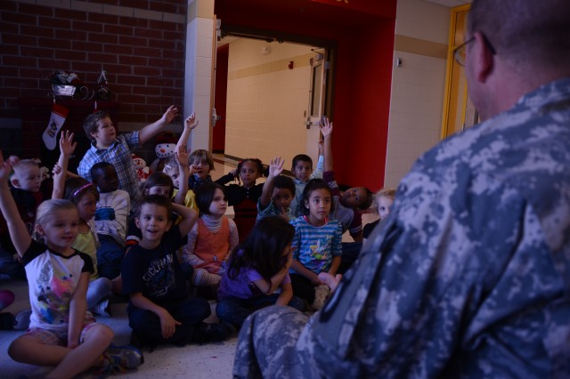 Spc. Paul Swank, a volunteer with the 7th Squadron, 17th Cavalry Regiment, interacts with students at Rossview Elementary School after reading a book Dec. 19. Swank was with four other Soldiers partnered with the school through the adopt-a-school program in hopes to help encourage reading among children. (U.S. Army photo by Sgt. Shanika L. Futrell, 159th Combat Aviation Brigade Public Affairs/RELEASED)