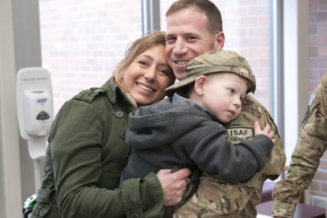 Valerie Kagan and her son Sean, hold tightly to their returning 2nd Brigade, 2nd Infantry Division Soldier, Sgt 1st Class Jeremy Kagan, after a welcome-home ceremony at Wilson Sports and Fitness Center, Joint Base Lewis-McChord-North, Wash., Dec. 16, 2012. This is the first group of 2nd Bde., 2nd Inf. Div., Soldiers to redeploy and have the good fortune to make it back home before the holidays.