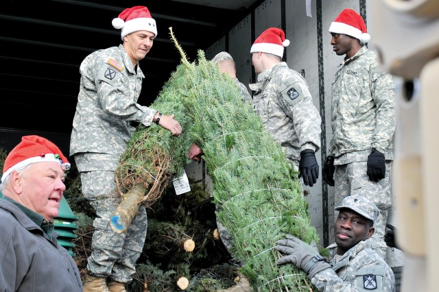 Maj. Gen. Stephen J. Townsend, Fort Drum and 10th Mountain Division (LI) commander, unloads Christmas trees from the back of a FedEx truck Thursday during the annual Trees for Troops program. Some 750 fir trees were delivered at no cost to Soldiers and their Family Members. Dick Darling, left, whose tree farm in Clifton Springs donates trees each year, helped unload trees along with Soldiers from 543rd Quartermaster Company, 548th Combat Sustainment Support Battalion.