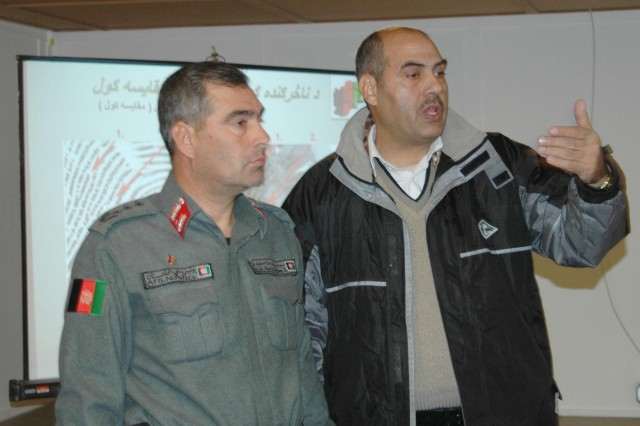 Col. Abdullah Khan, left, an officer from the Joint Regional Afghanistan National Security Forces Compound, and Col. Ramatullah Sediqi, the chief of the Criminal Investigation Division in Kandahar province, stress the importance of gathering evidence during a seminar at Kandahar Airfield Dec. 17.