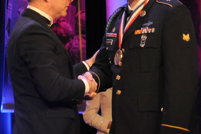 Spc. Bryan D. Dilberian Jr. receives the George Van Cleave Military Leadership Award from Lance Boxer during the 51st Annual USO Armed Forces Gala and Gold Medal Dinner on Thursday in New York City.