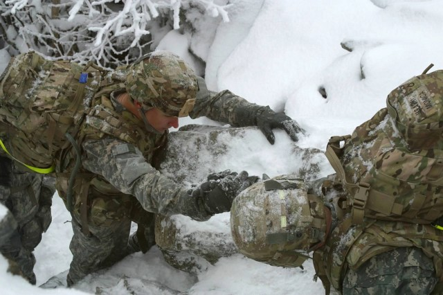 Pfc. Jacob Monica of B Company, 2nd BSTB, helps fellow Soldiers climb a hazardous part of the unit's trek up Whiteface Mountain.