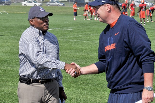 Floyd Little, former Denver Bronco and Pro Football Hall of Fame inductee, greets Syracuse University football coach Doug Marrone while visiting during the team's preseason training camp at Fort Drum in August. Little was a three-time All-American running back with Syracuse University in the 1960s.