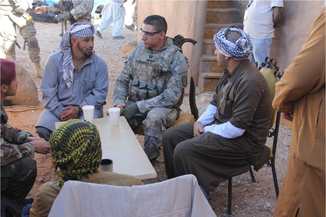 Role-played Afghan community leaders invite Capt. Joshua Yarbrough, center, 704th Engineer Company commander, to drink chai with them.