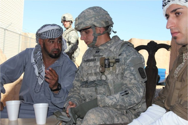 Capt. Joshua Yarbrough, center, 704th Engineer Company commander, and role-played Afghan community leaders discuss the 704th's involvement in the area.