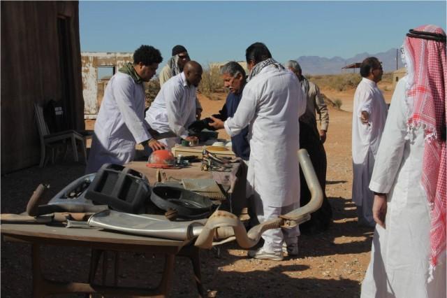 Afghan role players shop at a Karmen'Shah Village market.
