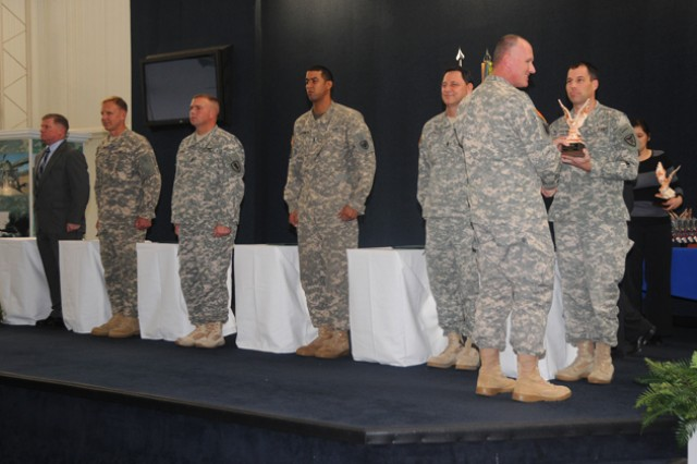"""Col. Kevin Christensen, president of the Army Aviation Center chapter of AAAA, gives a clay eagle to one of the instructors of the year, CW4 Ryan J. Rothmeyer. Other instructors of the year are James W. Jones, Phillip Schmiesing, Sgt. 1st Class Brandon J. Kroviak, W01 Alexander J. Chambers and CW3 Craig J. Johnson. (Not pictured"""" Capt. Ryan P. Welch)"""