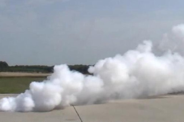 The photo shows a test of a full-size smoke grenade filled with the new composition developed at Picatinny Arsenal.