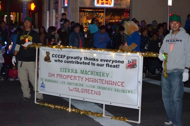 """Capt. Josepher Pacquing, left, and Sgt. 1st Class Oscar Romero, both with 1st Battalion, 360th Infantry Regiment, """"Task Force Warhawg,"""" 5th Armored Brigade, Division West, carry the sign introducing the Child Crisis Center of El Paso float in the 77th annual Celebration of Lights parade in downtown El Paso, Texas, Dec. 1. The unit partnered with the Crisis Center to build the float and participate in the parade. (Photo by Linda Stewart, 1st Battalion, 360th Infantry Regiment, """"Task Force Warhawg,"""" 5th Armored Brigade, Division West)"""