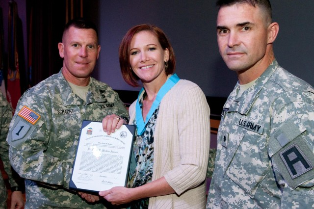 "Col. Eric Schacht, left, commander of Division West's 5th Armored Brigade, and Lt. Col. Thomas Kokes, commander of 1st Battalion, 362nd Air Defense Artillery Regiment ""Task Force Renegade,"" 5th Armored Brigade, pose with Heidi Kokes, who received the Dr. Mary Walker Award in a Dec. 10 ceremony at the U.S. Army Sergeants Major Academy at Fort Bliss, Texas. Kokes was recognized for her work in improving the quality of life for Soldiers and their Families. (Photo by Sgt. Edward Garibay, 16th Mobile Public Affairs Detachment)"