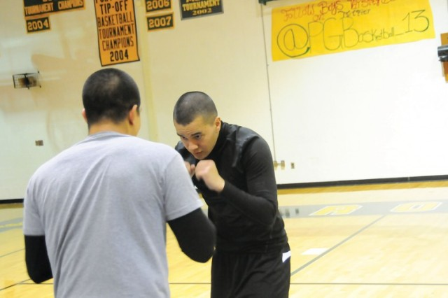 2nd Lt. Joseph McGee (black shirt) and 2nd Lt. Edwin Rodriguez, both Army Logistics University students, work on techniques during the Annual Day of the Warrior mixed martial arts seminar held Dec. 15 at Prince George High School.
