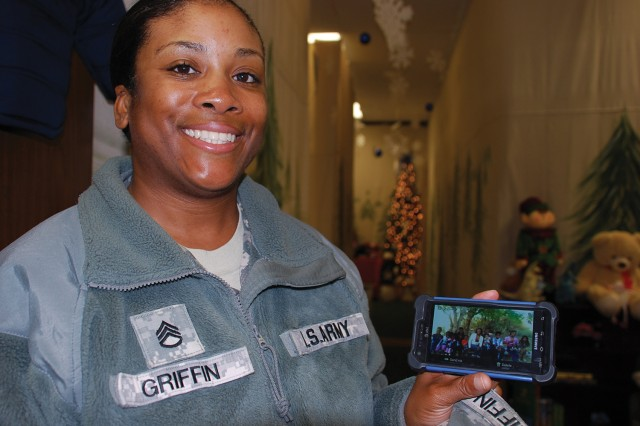 Staff Sgt. Ariesa Griffin, Romeo Company, 262nd Quartermaster Battalion, 23rd QM Brigade, shows a picture of her extended family while at the annual Holiday Helper toy store. Griffin is responsible for nine children, including those of her sister who died in February.