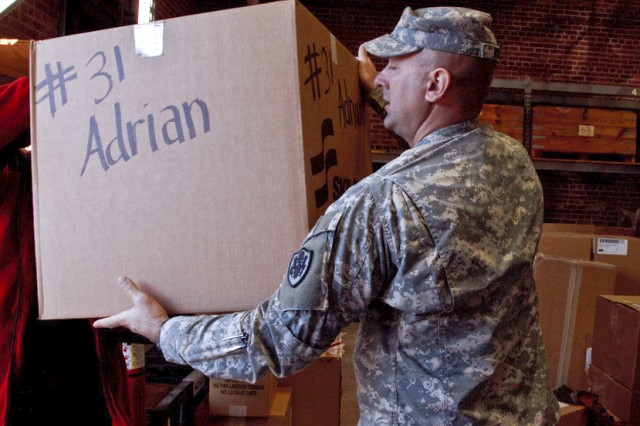 Lt. Col. Robert Rouse, commander of DLA Distribution Anniston, Ala., passes box of presents to a truck that will take the gifts to the Calhoun County Department of Human Resources Dec. 19. The gifts are part of the depot's Christmas Cheer program, which gives presents valued between $150 and $175 to children in protective custody at DHR. The children are anonymous, known to the givers only by a first name, a number and their age.