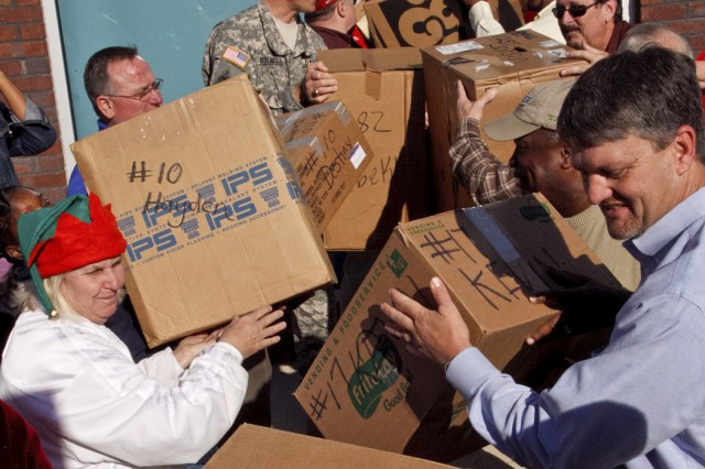 Anniston Army Depot employees unload boxes of presents from a truck at the Calhoun County Department of Human Resources Dec. 19. The gifts are part of the depot's Christmas Cheer program, which gives presents valued between $150 and $175 to children in protective custody at DHR. The children are anonymous, known to the givers only by a first name, a number and their age.