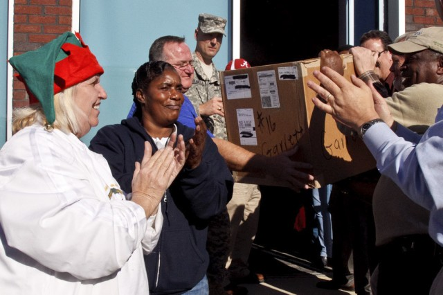 Anniston Army Depot employees applaud as the last box of presents is removed from a truck at the Calhoun County Department of Human Resources Dec. 19. The gifts are part of the depot's Christmas Cheer program, which gives presents valued between $150 and $175 to children in protective custody at DHR. The children are anonymous, known to the givers only by a first name, a number and their age.