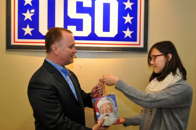 To support those who serve far away from home during the holiday season, members of Seoul American Middle School's National Junior Honor Society donated $2,000 worth of phone cards to the local USO, Dec. 18, 2012. Stephanie Choe, president of National Junior Honor Society at Seoul American Middle School, right, hands the phone cards to Tony Davis, country director for USO Korea.
