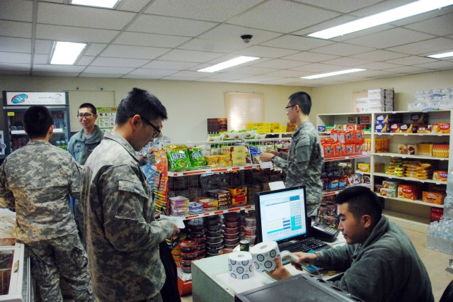 "At Camp Red Cloud's KATUSA PX, managing clerk Pfc. Kim Dong-hyun (seated) waits on a customer, Cpl. Lee Chan-ho Nov. 15. Although the store serves mainly KATUSAs "" South Korean Soldiers assigned to the U.S. Army "" Americans too shop there. It's similar to the convenience stores found everywhere in South Korea, stocking frozen foods, snacks, water and other beverages, and such staples as razors, shampoo and soap. Kim is with Headquarters and Headquarters Battalion, 2nd Infantry Division, Lee with Headquarters and Headquarters Company, U.S. Army Garrison Red Cloud. "" U.S. Army photo by Pfc. Lee Seong-su"