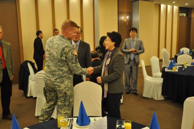 Col. Michael E. Masley, garrison commander for USAG Yongsan, and Hong Mi-young, Bupyeong-gu mayor, greet each other during the Bupyeong-gu Korean American Friendship Council meeting, Dec. 20. (U.S. Army photo by Cpl. Lee Hyokang)
