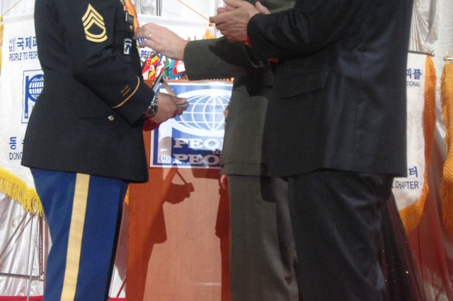 Sgt. 1st Class Jacob Anthony Aguilar, noncommissioned officer-in-charge of the Directorate of Human Resources for U.S. Army Garrison Yongsan, receives an award from Maj. Gen. Michael R. Regner, the commander of the U.S. Marine Forces Korea, during the People to People International's 40th Annual Award Banquet and International Peace Festival at the Westin Chosun Hotel, Dec.18. Aguilar voluntarily supported various Good Neighbor Program activities, including Charcoal delivery to the Seoul community. (Photo by Sgt. Kevin Frazier)