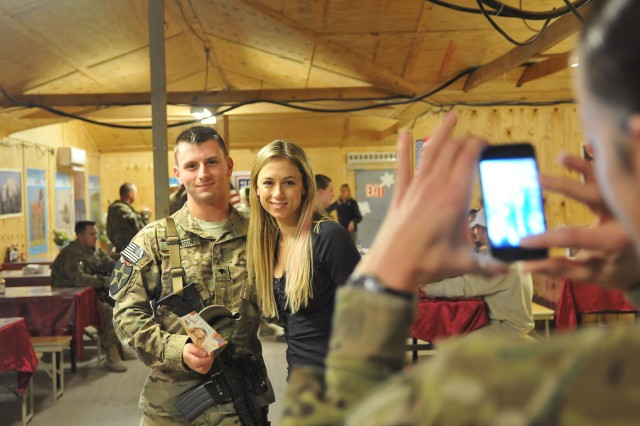 A Soldier with the 4th Stryker Brigade Combat Team, 2nd Infantry Division, poses with comedian Iliza Shlesinger during a USO tour, Dec. 16, 2012, at Forward Operating Base masum Ghar, Afghanistan.