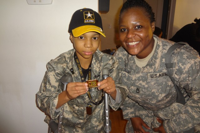 Khalil Quarles shows off his Army Medical Command coin that Sgt. 1st Class Stephanie P. Abdullah delivered on behalf of the Surgeon General. Abdullah an OTSG civilian is also an Army Reserve Soldier assigned to the Office of the Chief Army Reserve. (Photo courtesy of Army Medicine)