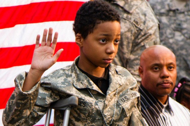 Khalil Quarles, 10, raises his right hand during his honorary enlistment into the Army Reserve as his father, Damon, watches the ceremony, held in Baltimore. Maj. Gen Sanford Holman, 200th Military Police Command's commanding general, read the special Oath of Enlistment for Quarles, who suffers from a rare form of cancer.