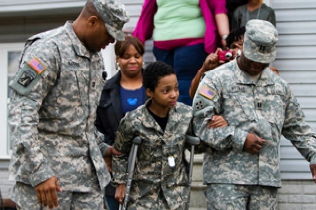 Army Reserve Capt. John Barbee and Capt. Sherman Pittman assist Khalil Quarles, 10, down the sidewalk outside his home in Baltimore, during a surprise visit from members of the 200th Military Police Command, and the Office of the Chief, Army Reserve.